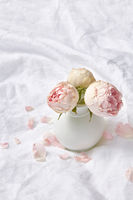Ceramic vase with roses on a sheet.