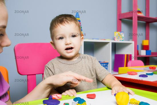 The baby boy learns to create plasticine figures in kindergarten