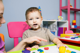 The baby boy learns to create plasticine figures in kindergarten