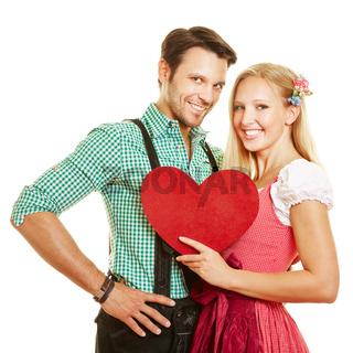 Paar in bayrischer Tracht hält rotes Herz