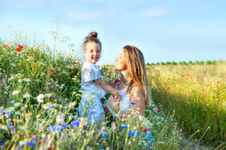 Mom and her pretty little daughter in a summer meadow