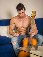 Muscular young man playing guitar sitting on couch