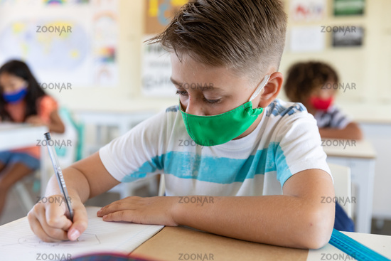 Boy wearing face mask writing while sitting on his desk at school