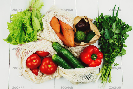 Fresh vegetables in eco bags on white table
