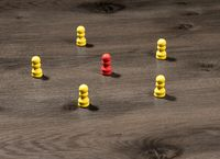 Yellow wooden pegs surrounding red one to illustrate leadership or social media communication