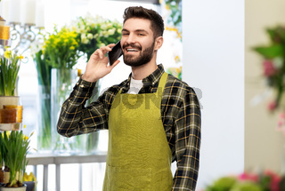 male seller calling on smartphone at flower shop