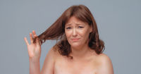 Unhappy beautiful woman holds of hair ends looking at camera. Pretty nude mature woman on gray back. Hair care concept
