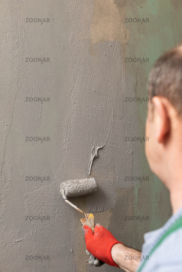 In the bathroom, a general construction worker applies moisture insulation using a roller.