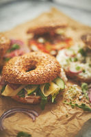 Bagel sandwiches with various toppings, salmon, cottage cheese, hummus, ham, radish and fresh herbs
