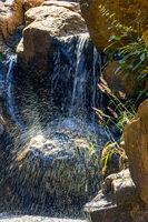 Small waterfall shining between stones