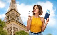 happy woman with air ticket over eiffel tower