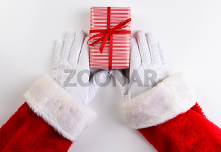 High angle shot of Santa Claus hands with a red and white striped Christmas Present.
