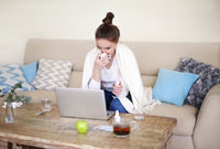 Sick woman sitting on sofa near the computer trying to work at home
