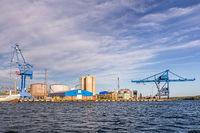 Massive blue cranes unload cargo in a seaport in Sweden