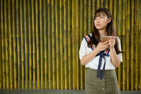 Young beautiful Asian teenage girl thinking while using phone against bamboo fence