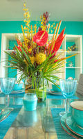 Tropical blue table set with flowers including Heliconia bihai, yellow oncidium orchids