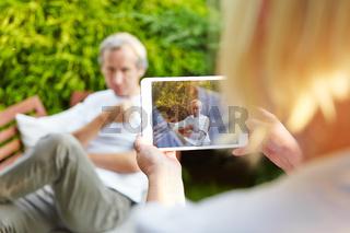 Frau fotografiert Mann mit Tablet PC