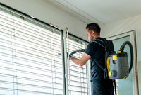 professional cleaner vacuum cleaning window blinds in an apartment in a high-rise building