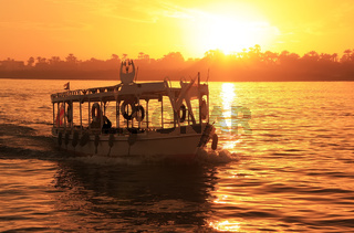 Boat cruising the Nile river at sunset, Luxor