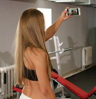 Beautiful girl doing selfie on smartphone in gym