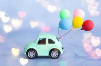 Kleines gruenes Auto mit Luftballons