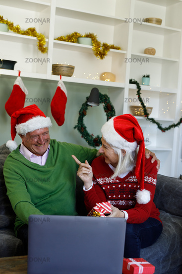 Senior couple in santa hat laughing and pointing at each other while siting on couch at home