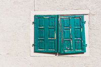 Old dilapidated weathered green wooden shutters