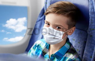 boy in medical mask travelling by plane