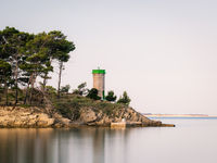 Pine trees and lighthouse on a small island on rab Croatia