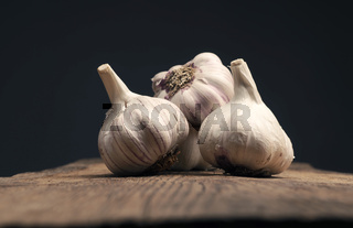 Four bulbs of garlic on a rustic kitchen table