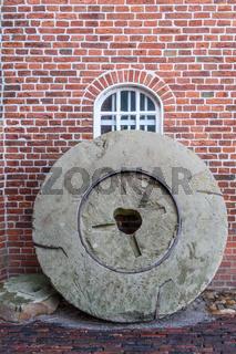 Alter Mühlstein an einer Windmühle stehend, Ostfriesland, Niedersachsen, Deutschland
