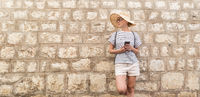 Beautiful young female tourist woman standing in front of old textured stone wall at old Mediterranean town, smiling, holding, smart phone to network on vacationes. Copy space