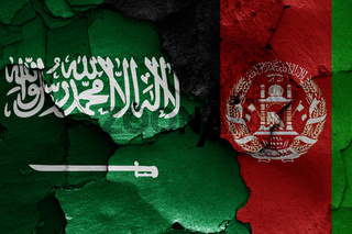 flags of Saudi Arabia and Afghanistan painted on cracked wall