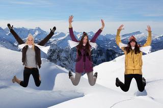 Junge Frauen springen im Winter in den Bergen im Schnee