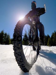 Mountainbiker riding snowy trail in winter.  Biker  on bike in deep snow