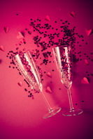 Two champagne glasses with splash of red heart shaped confetti on red background. Overhead view