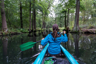 female kayaker enjoys paddling through the channels and canals o the Spreewald region in Germany