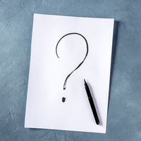 Question mark, written in ink on a piece of standard office paper, overhead square shot on a blue background