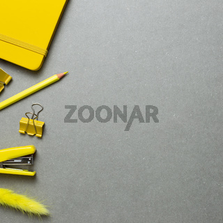 Yellow stationery office supplies. Notebook, clip, pencil, stapler on gray background. flat lay, top view, copy space