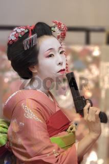 Pretty young Geisha maiko girl in kimono holding a plastic gun in her hand.