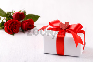 White gift box red ribbon and roses