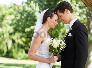 Newly wed couple with head to head in garden