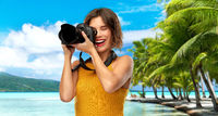 happy woman photographer with camera on beach