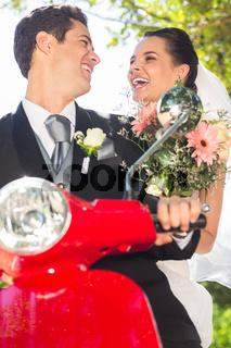Newlywed couple enjoying scooter ride