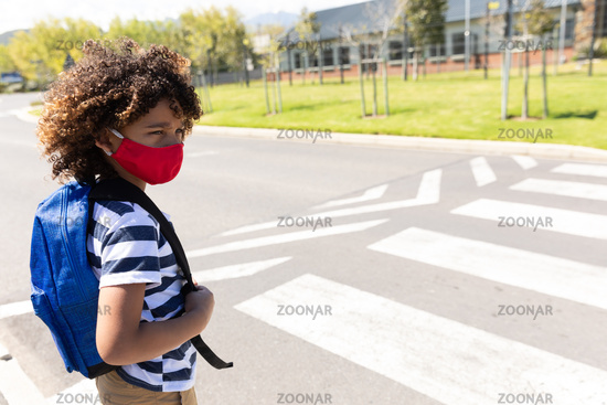 Boy wearing face mask standing on the road