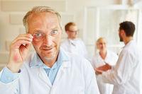 Gruppe Ärzte hinter Chefarzt mit Brille