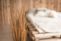 Decorative straws for the bedroom. On a blurred background a light bed. Cozy bedroom. High quality photo