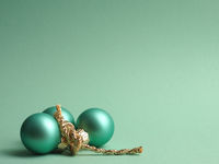 Three turquoise vintage Christmas baubles on a turquoise background