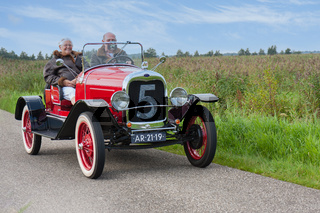 Senior couple riding with classic Ford car in the Netherlands