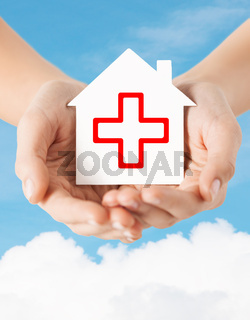 hands holding paper house with red cross